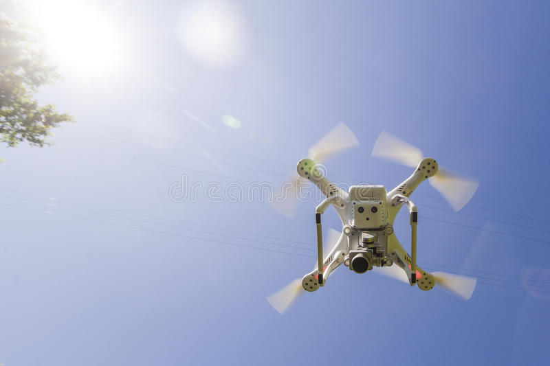 White drone hovering in a bright blue sky bottom view royalty free stock photo