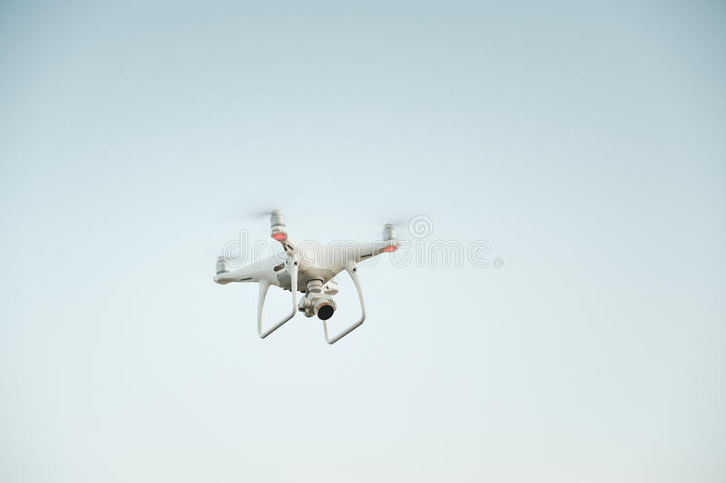 White drone hovering in a bright blue sky royalty free stock image