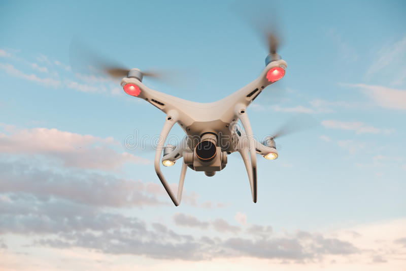 White drone hovering in a bright blue sky royalty free stock photos