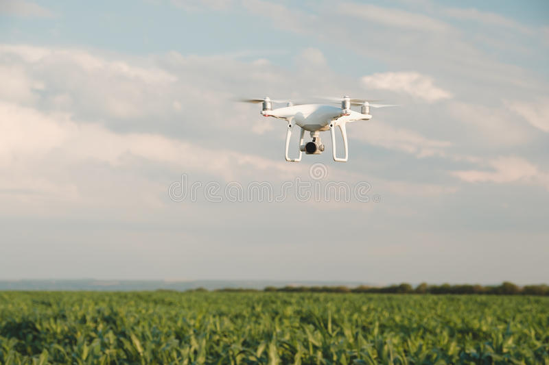 White drone hovering in a bright blue sky royalty free stock images