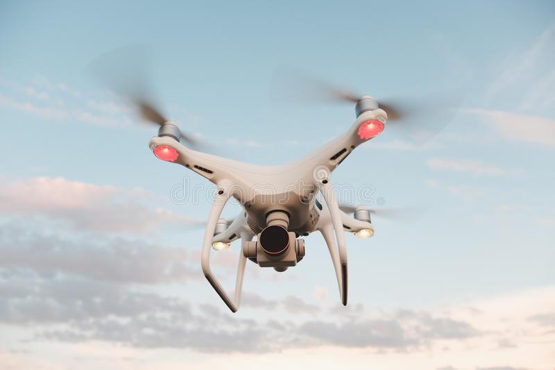 White drone hovering in a bright blue sky royalty free stock photo