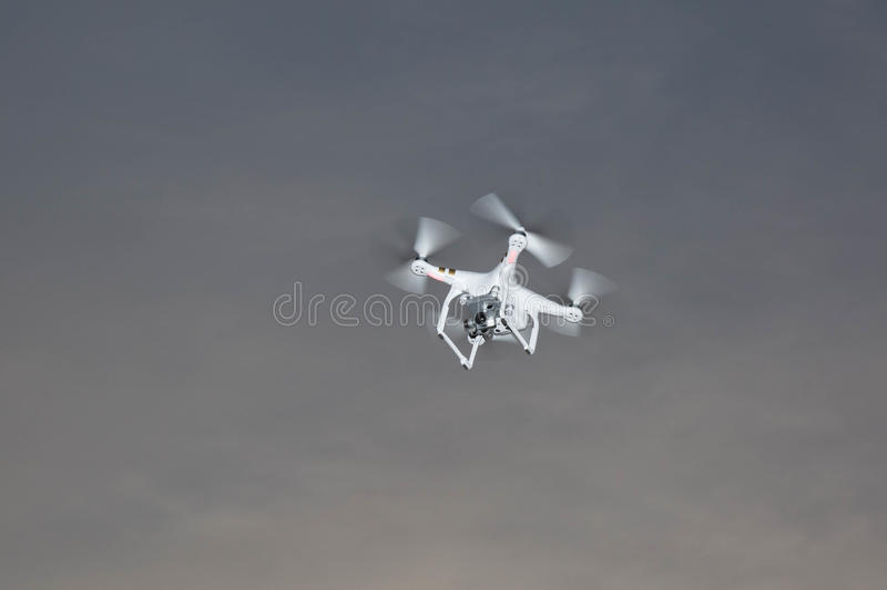 White drone hovering. In a bright grey sky royalty free stock photo