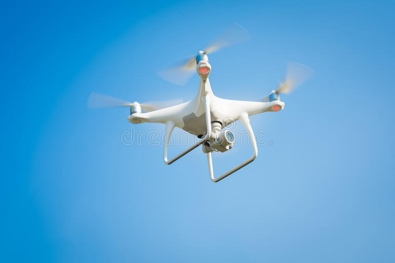 White drone hovering in a bright sky royalty free stock photo