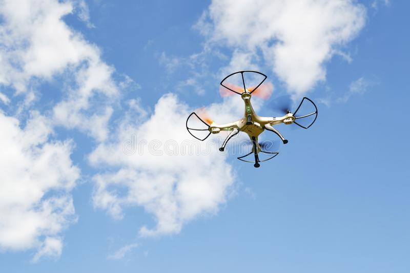 White drone hovering in a. Bright blue sky stock images