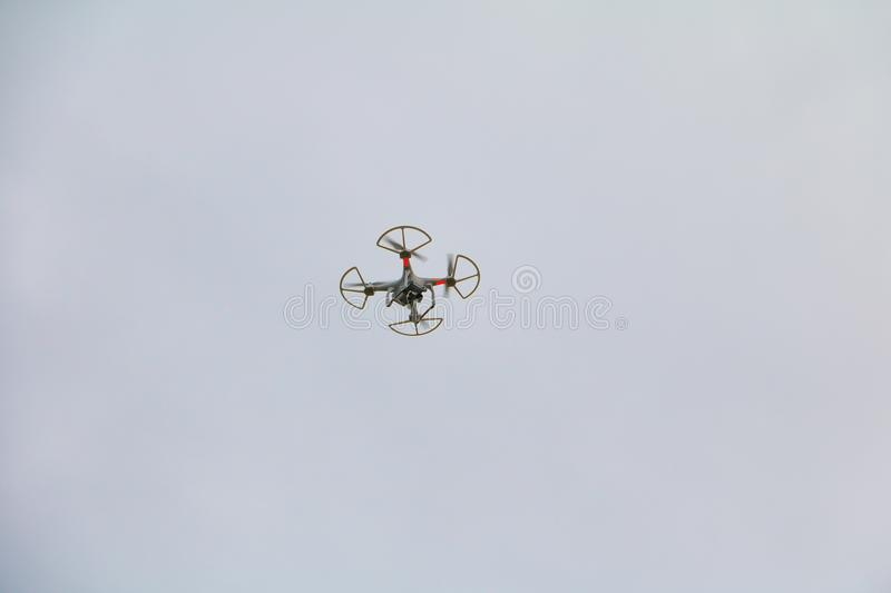 White drone motion hovering with photo camera flying in sky stock photos