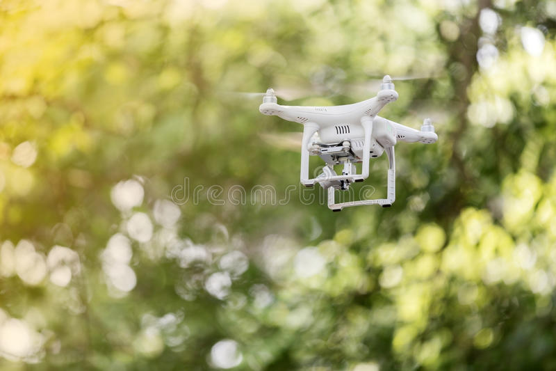 White drone quad copter with high resolution digital camera flying in the blue sky ,soft focus stock photography