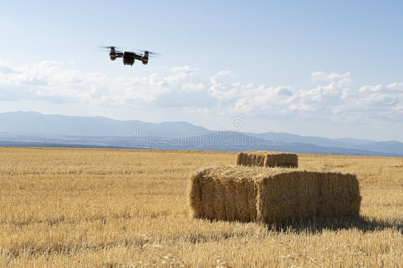 White drone with red lights flying over a field of mowed cereals with straw bales and mountains on the horizon.drone flight stock photos