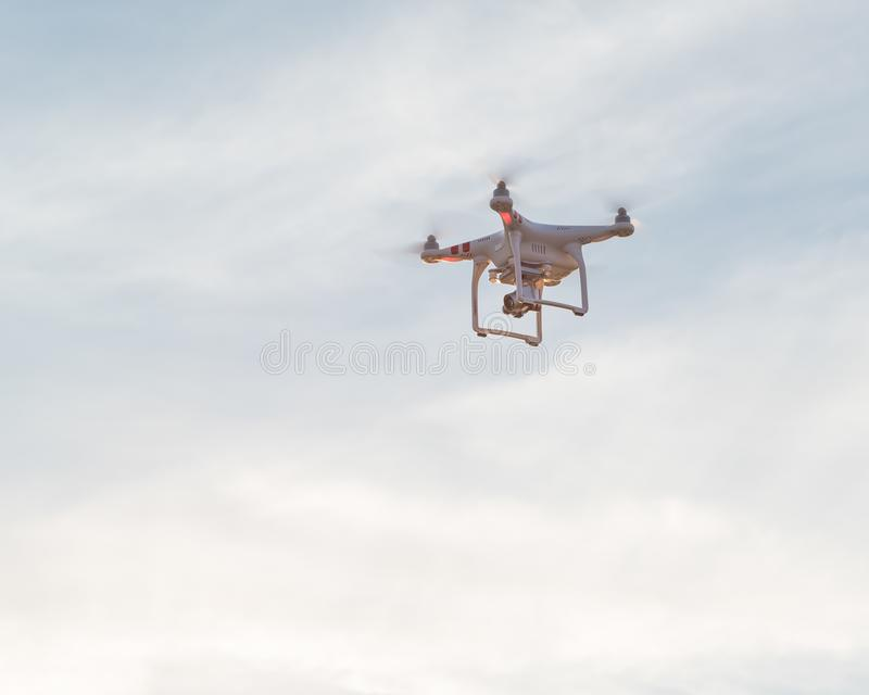 White drone sillhouste flying cloud blue sky stock image