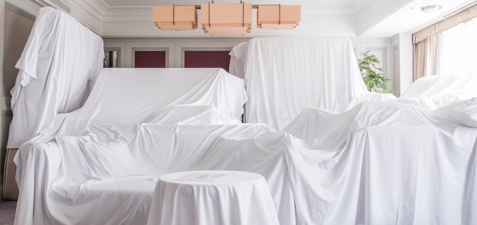Furniture Dust Covers. White dust cover cloth covering furnitures in a room royalty free stock photography