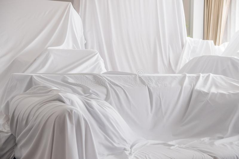 Furniture Dust Covers. White dust cover cloth covering furnitures in a room royalty free stock images