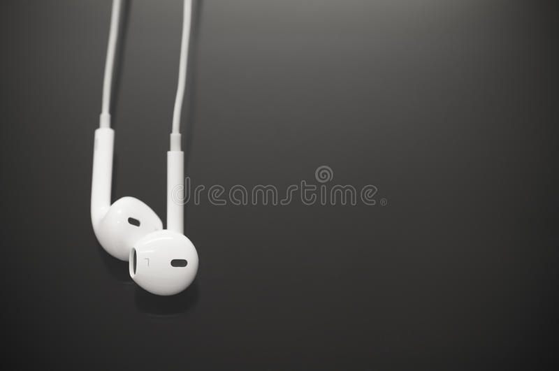 White earbuds. On black screen background royalty free stock images