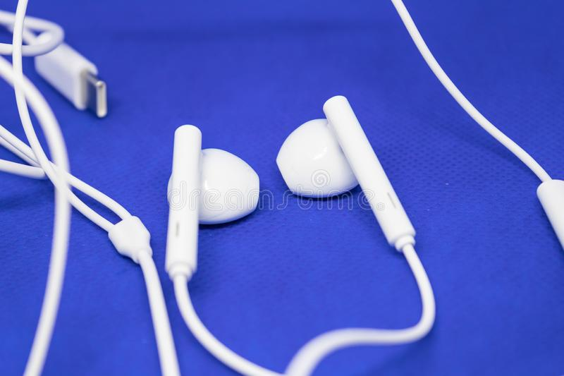 White earpods on blue background with the cable, music listening devices concept - Image. White earpods on blue background with the cable, music listening stock photo