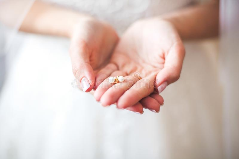 White earrings in hands of the bride royalty free stock image