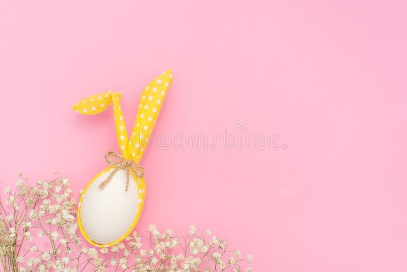 White Easter egg with Bunny ears on pink background stock image