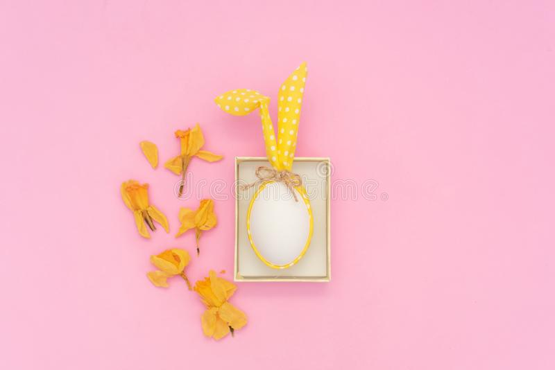 White Easter egg with Bunny ears on pink background royalty free stock images