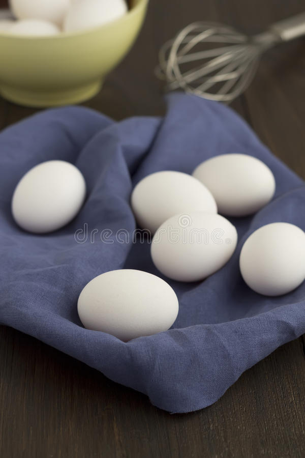White egg on blue cloth with whisk and bowl on a wooden table. royalty free stock image