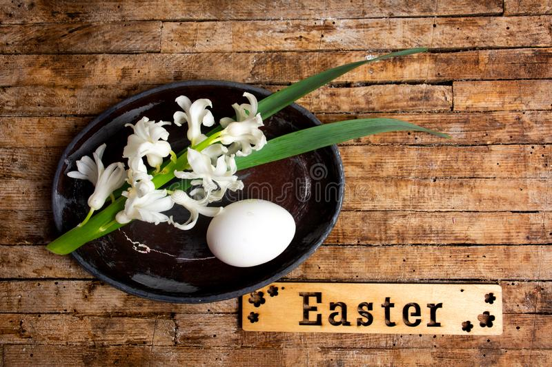 White egg and hyacinth flowers with Easter note stock image