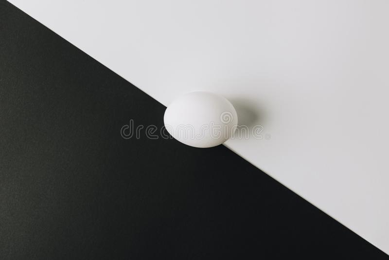 White egg laying in middle of black and white background stock image