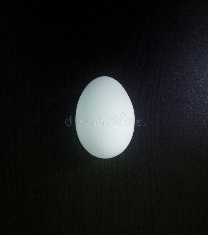 White egg on the table. White egg table black oval stock photo