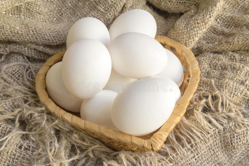 White eggs close up. White eggs in a straw plate against the background of the canvas stock images
