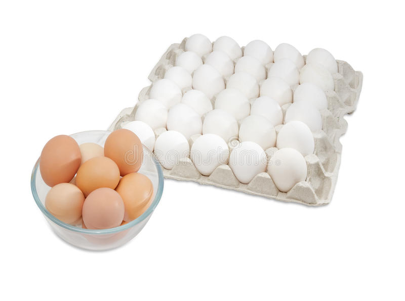 White eggs in egg tray, brown eggs in glass bowl royalty free stock photo