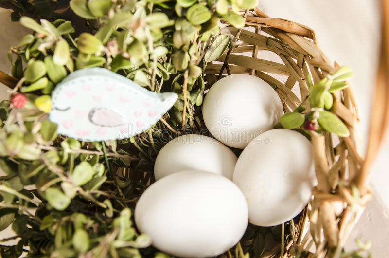 White eggs on grass. Beautiful white eggs in a basket with grass and birdie near basket royalty free stock photo