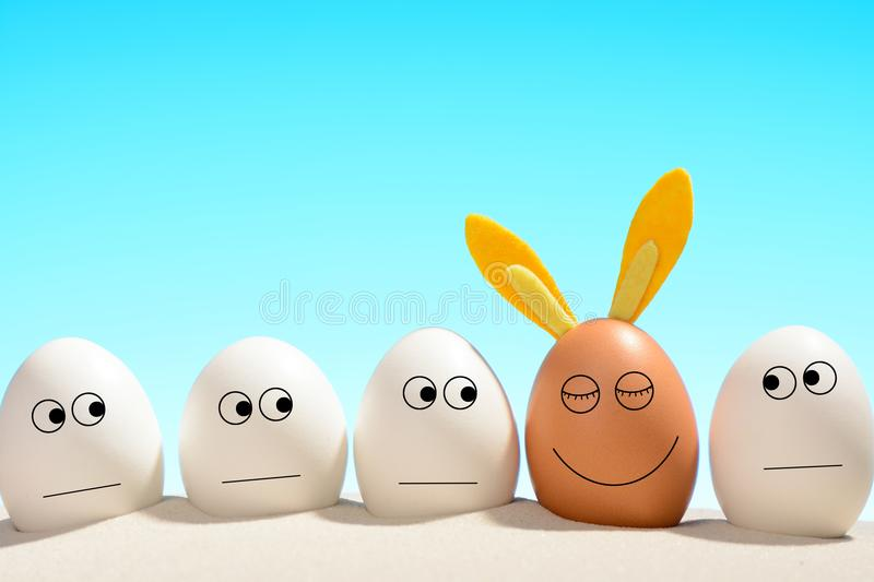 White eggs, looking the brown tanned with rabbit ears. Easter on the beach concept. stock photos