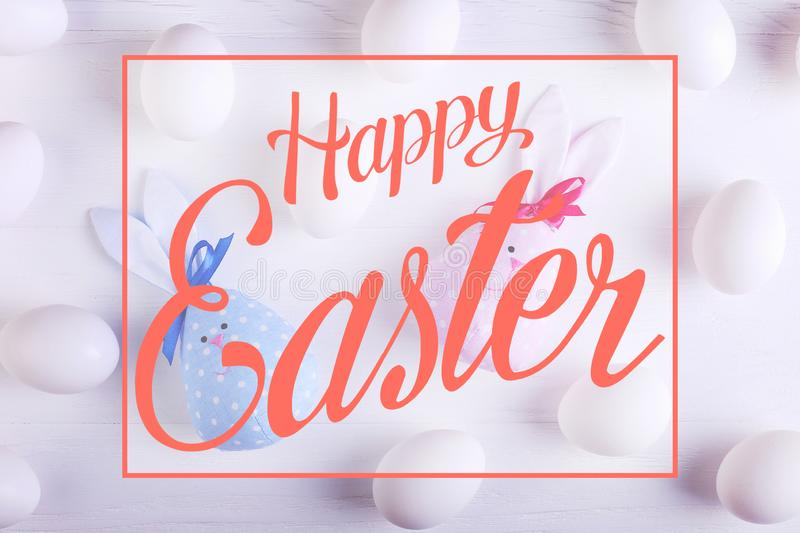 White eggs pattern, including two handmade Easter bunny, blue and pink. Text, happy easter stock images