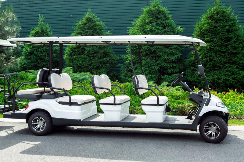 White electric car for transportation of passengers in the golf club. White electric car for transportation of passengers in the golf club on the background of stock photos