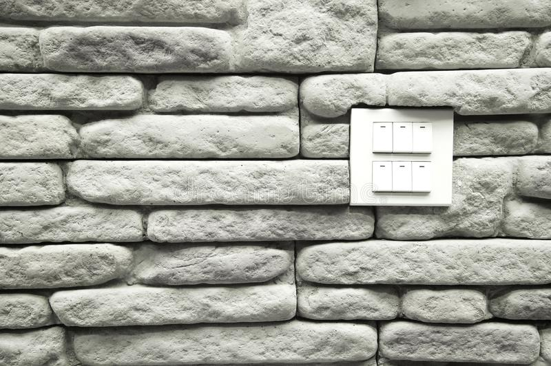 White electric lamp switch for turn on with grey stone brick wall architecture background. Six white electric lamp switch for turn on with grey stone brick wall royalty free stock photos