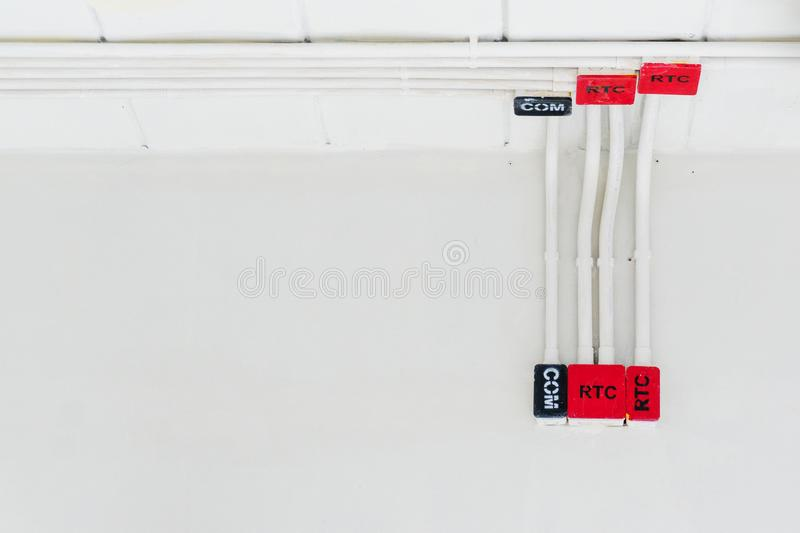 White electric PVC pipe in red and black are connected to power lines or electrical wires, Ethernet UTP cables, internet and light royalty free stock image