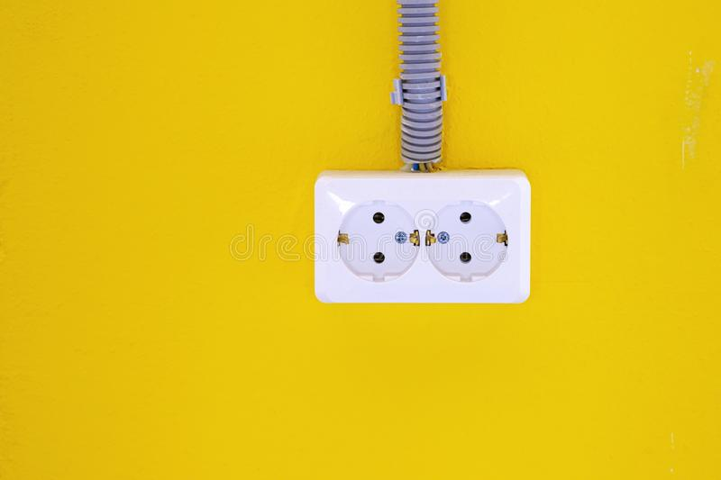 White electric socket on the yellow wall. Socket on the yellow wall. Copy space. stock photo