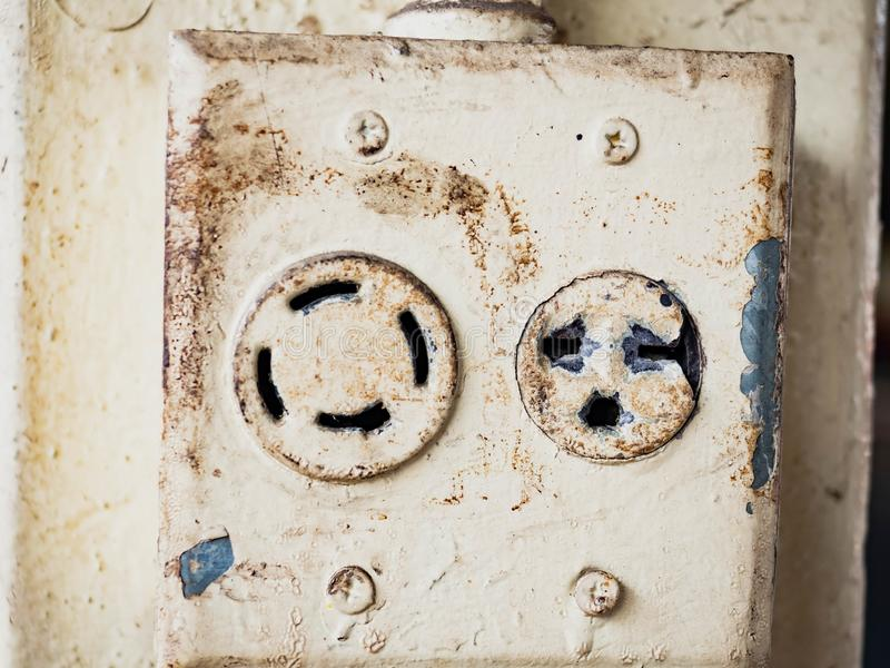 White electrical plug in the electric socket on a wall stock photo