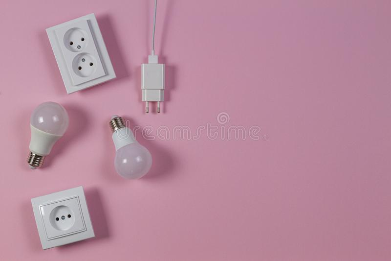 White electrical power sockets, power plugs, light lamp bulbs on light pink background. Top view stock photography