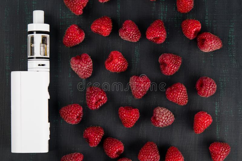 White electronic cigarette is surrounded by berries of red raspberries on a black background stock photos