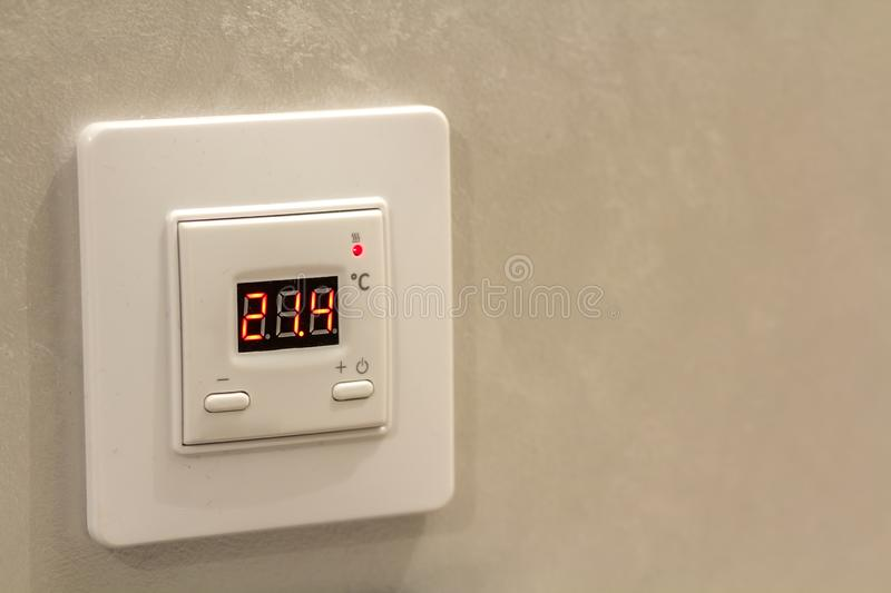 White electronic programmable digital thermostat on light wall copy space background. Climate control, comfortable home stock photos