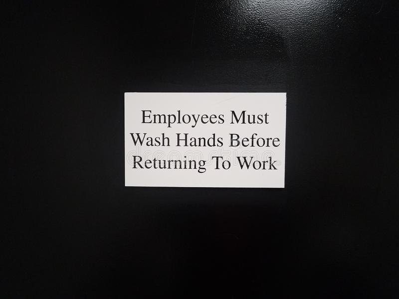 White employees must wash hands before returning to work sign on black door stock images