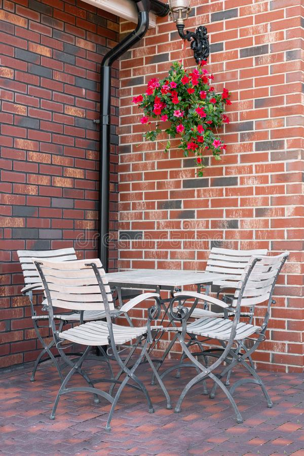 White Empty Cafe Table and Chairs in Corner in front of Brick Wall stock photo