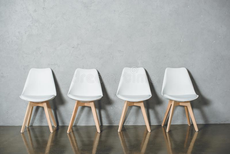 White empty chairs for job interview standing in line in hall stock images