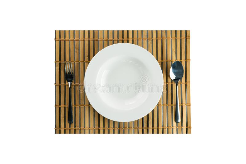 White empty dish with stainless spoon and fork. On bamboo weave on isolated background in top view royalty free stock photography