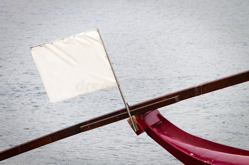 White Empty Flag on Boat Bow. White empty flag ready for text on boat bow against river background stock images