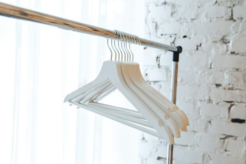 White empty hangers against a white brick wall background stock photos