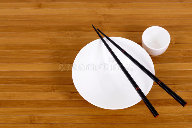 White empty japanese rice bowl and sake cup chopsticks. White empty rice bowl and sake cup with black chopsticks on a bamboo background royalty free stock photography