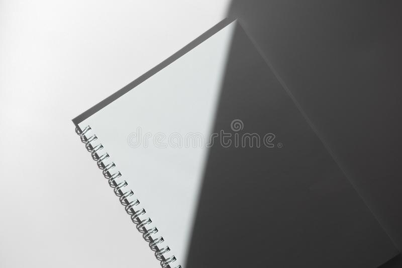 White empty paper notebook with spiral on white desk and gray shadow, top view. Mockup clean sheet. Minimalism stock photo