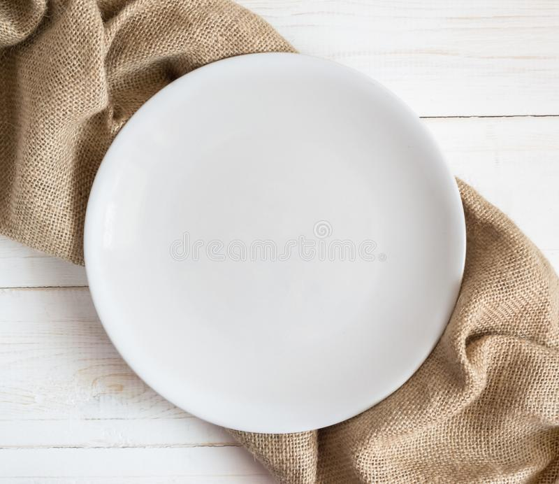 White empty plate on wooden table with brown napkin stock photo