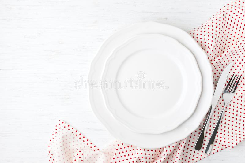White empty plates on checked napkin. White empty plates and cutlery on polka dot napkin on white wooden table. Setting table top view stock photo
