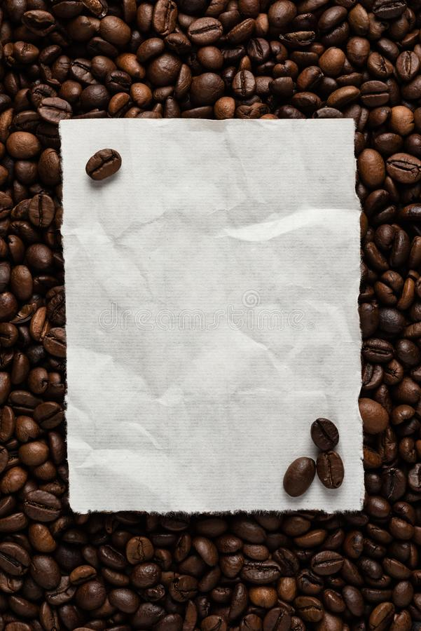 White empty sheet of paper on the background of roasted coffee beans for text menu or recipe royalty free stock image