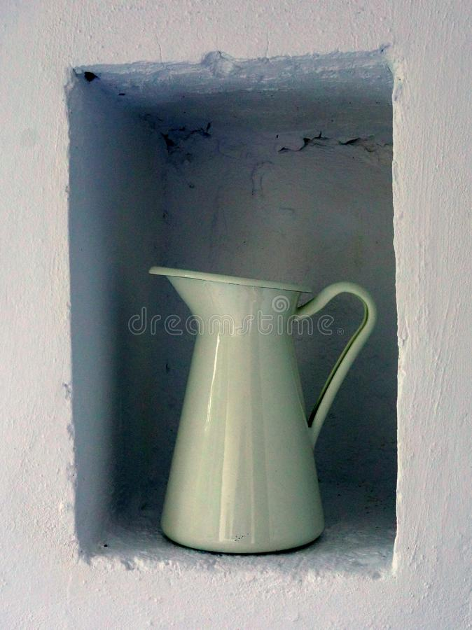 White Enamel Jug in White Nook. A white enameled milk jug in a white painted wall nook or cavity royalty free stock photo