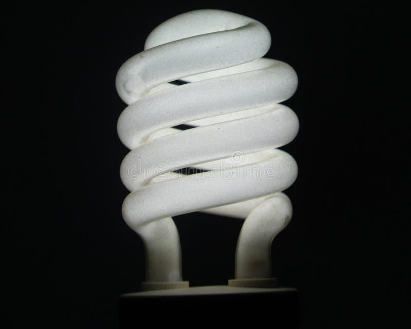 A white energy saving bulb and blacked background stock image