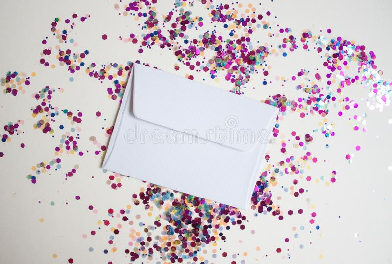 White envelop on light festive background. With sparkles. Flat lay style royalty free stock photos